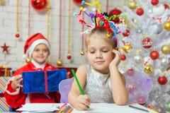 她给圣诞老人写一封信,坐与在她后的一件礼物 免版税库存照片