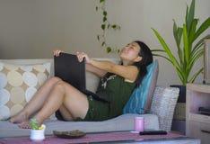 她20s或30s坐愉快在客厅家沙发长沙发工作或使用的co年轻美丽和轻松的亚裔中国妇女 图库摄影