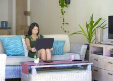 她20s或30s坐愉快在客厅家沙发长沙发工作或使用的co年轻美丽和轻松的亚裔中国妇女 免版税图库摄影