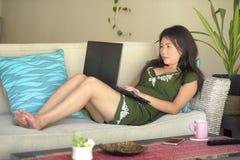 她20s或30s说谎愉快在客厅家沙发长沙发工作或使用的comp年轻美丽和轻松的亚裔中国妇女 免版税库存照片