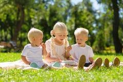 好一起坐在公园全部的女孩和男孩 免版税库存图片