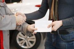 好交易 震动在汽车前面的手的特写镜头射击 免版税库存图片