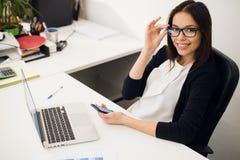 好企业谈话 玻璃的快乐的年轻美丽的妇女谈话在手机和使用有微笑的膝上型计算机,当时 免版税图库摄影