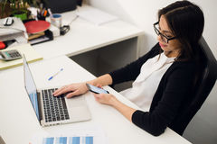 好企业谈话 玻璃的快乐的年轻美丽的妇女谈话在手机和使用有微笑的膝上型计算机,当时 库存图片
