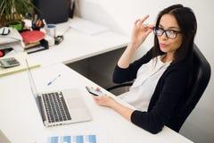 好企业谈话 玻璃的快乐的年轻美丽的妇女谈话在手机和使用有微笑的膝上型计算机,当时 免版税库存照片