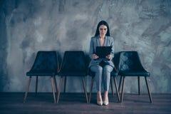 好典雅的时髦的时髦别致的在工业顶楼的高级主管经理深色的夫人坐的等待的任命 库存照片