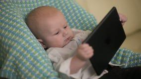 好奇严肃的婴孩在他的手上坐儿童` s椅子举行片剂 特写镜头 股票录像