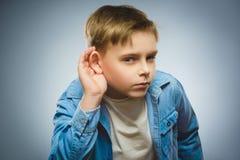 好奇失望的男孩听 儿童听力某事,对耳朵姿态的手 库存图片