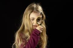 好奇小女孩的放大镜 免版税图库摄影
