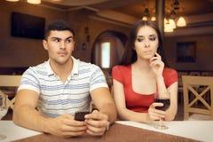 好奇智能手机的女孩暗中侦察的男朋友 免版税图库摄影