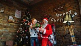 好奇男孩从圣诞老人接受礼物在装饰的欢乐室和热心地跑掉打开 影视素材
