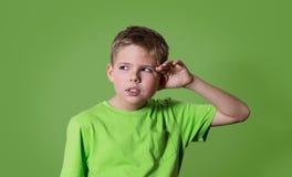 好奇男孩听 特写镜头画象儿童听力某事,父母谈话,闲话,在绿色对耳朵姿态的手隔绝的 库存照片