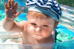 好奇,愉快,十个月摆在蓝色水池的婴孩 免版税库存图片