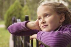 好女孩凝视室外在紫色背心在秋天 免版税库存照片