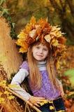 好女孩在倾斜反对树的秋天公园站立 在秋叶被编织的花圈头  免版税库存图片