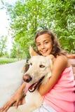 好女孩拥抱她的狗坐长凳 免版税库存照片