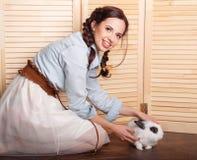 好女孩用在她的胳膊的一只兔子 免版税库存图片