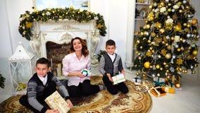 好妇女和母亲和孩子有男孩的看并且微笑照相机与礼物在他们的手上在好心情并且坐  影视素材