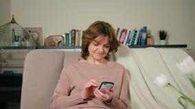 好妇女在一间舒适屋子使用在智能手机的app坐沙发 股票录像