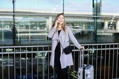 好妇女站立与valise和谈话由smartpone在机场附近 库存图片