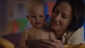 好婴孩坐在与他的母亲的坏的和她显示他与她的电话的动画片 影视素材