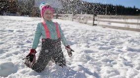 好小女孩充当雪在冬天假期时在山的乡下 逗人喜爱的孩子是 影视素材