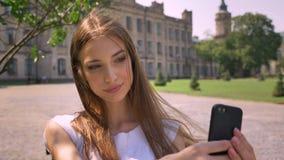 好少妇在公园在智能手机站立自白天,做selfie,微笑,通信概念 影视素材