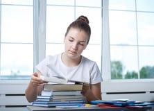 好少年青少年的女学生坐在与嘘的桌上 免版税库存照片