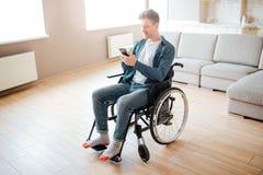 好年轻人以包括和伤残 坐轮椅 在手上拿着电话和看它 ?? 免版税库存照片