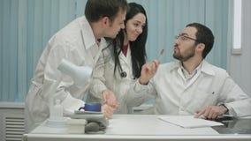 好心情的两位医师谈论某事在互联网在医疗中心,然后来实习生 免版税图库摄影