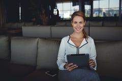 好心情的女性使用数字式片剂,当等待她的顺序在舒适的餐馆时 免版税库存照片