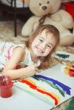 好心情绘画彩虹的女孩与刷子的 免版税库存图片