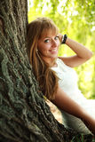 好快乐的微笑的女孩在结构树下 免版税库存图片