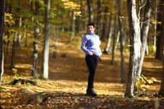 好成熟妇女在黄色秋天背景站立  秋天森林的成熟妇女 库存图片