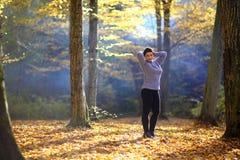 好成熟妇女在黄色秋天背景站立  秋天森林的成熟妇女 免版税库存照片
