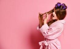 好挑剔的少女或青少年的女孩在她的头发吓唬与她的头发情况或某事困住的温泉沙龙的 免版税库存图片