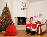 好新年精神:圣诞树、礼物袋子、壁炉和装饰 圣诞老人和两个孩子 免版税库存照片