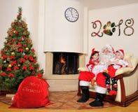 好新年精神:圣诞树、礼物袋子、壁炉和装饰 圣诞老人和两个孩子 免版税库存图片