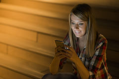 好消息 年轻愉快的妇女微笑的发短信在她的电话 免版税库存照片