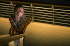 好消息 美丽的女孩检查某事在她巧妙的电话 免版税图库摄影
