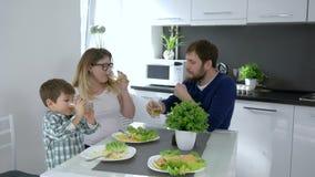 好父母,在手中叮当响与饮料的快乐的家庭在早餐期间 股票录像