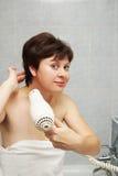好的中部年迈的妇女在卫生间里烘干她的头发 免版税库存照片