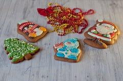 好的圣诞节甜点 在圣诞老人、雪人、放置在装饰小珠附近的杉树和企鹅形状的蜂蜜曲奇饼在轻的woode 库存照片