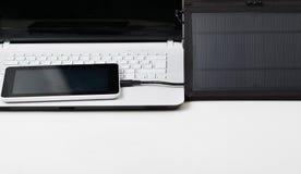 好的黑便携式的太阳坐在专属白色膝上型计算机,现代事务顶部的充电器和一种小片剂 免版税库存图片