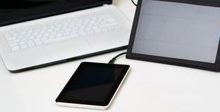 好的黑便携式的太阳坐在专属白色膝上型计算机,现代企业技术旁边的充电器和一种小片剂 免版税库存照片