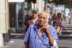 好,法国2017年8月15日:老人谈话在手机在商业街区域 免版税库存照片