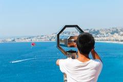 好,法国- 16 09 16 :看通过在一个飞行降伞的双筒望远镜的男孩在美丽的海在尼斯,法国 免版税库存照片