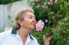 好年长妇女嗅到的花在庭院里在一个温暖的夏日 库存图片