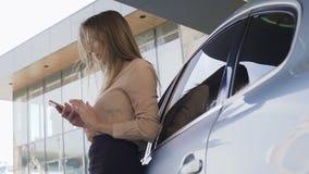 好businesslady聊天与智能手机的,站立的近的汽车客户 股票录像