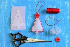 如何做毛毡圣诞树集合 毛毡圣诞树工艺,纸模板,螺纹,针,在一张木桌上的剪刀 免版税库存图片